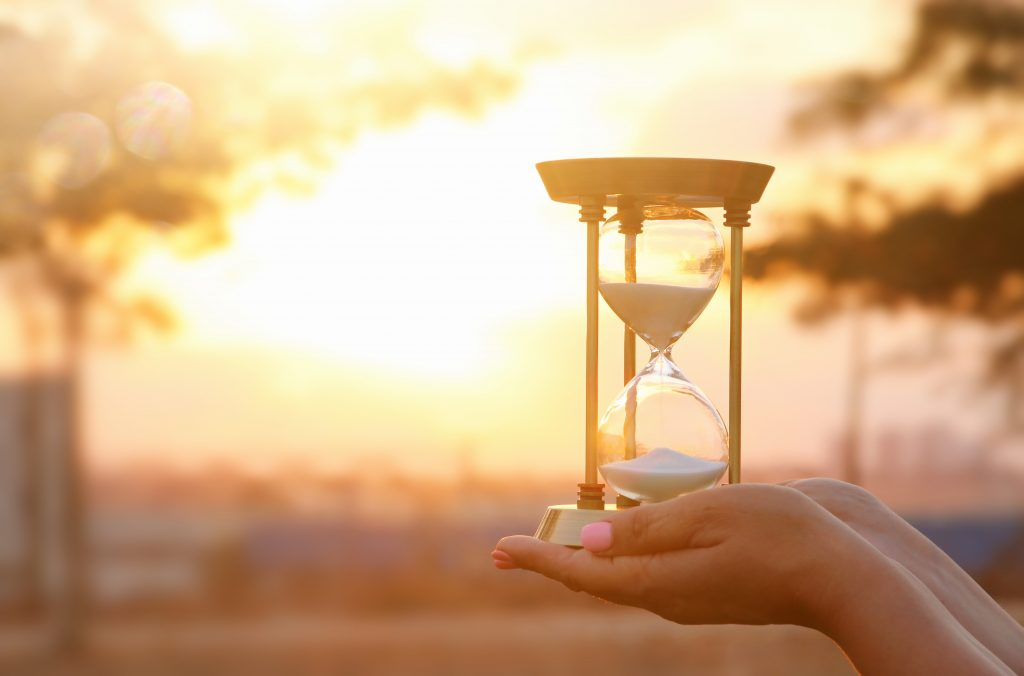 Young woman holding Hourglass during sunset. vintage style